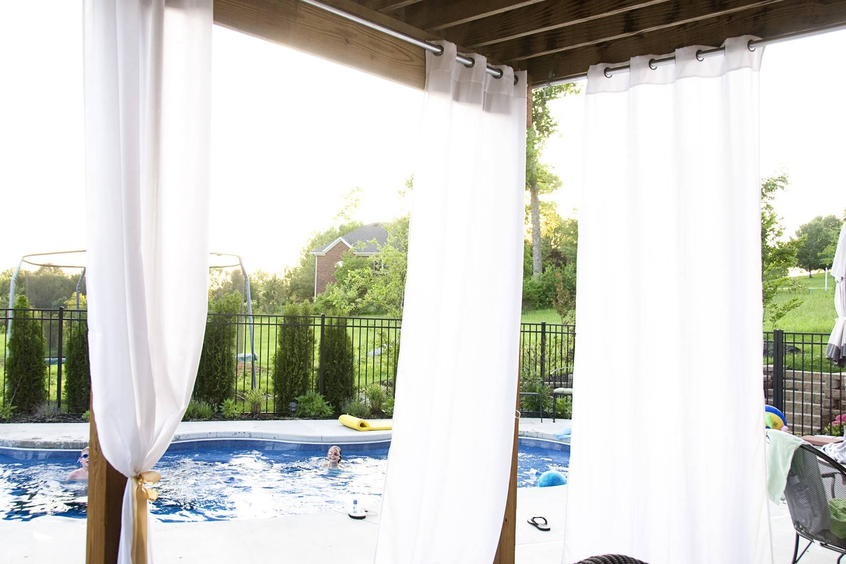 White drapes hanging from wood deck with pool in background