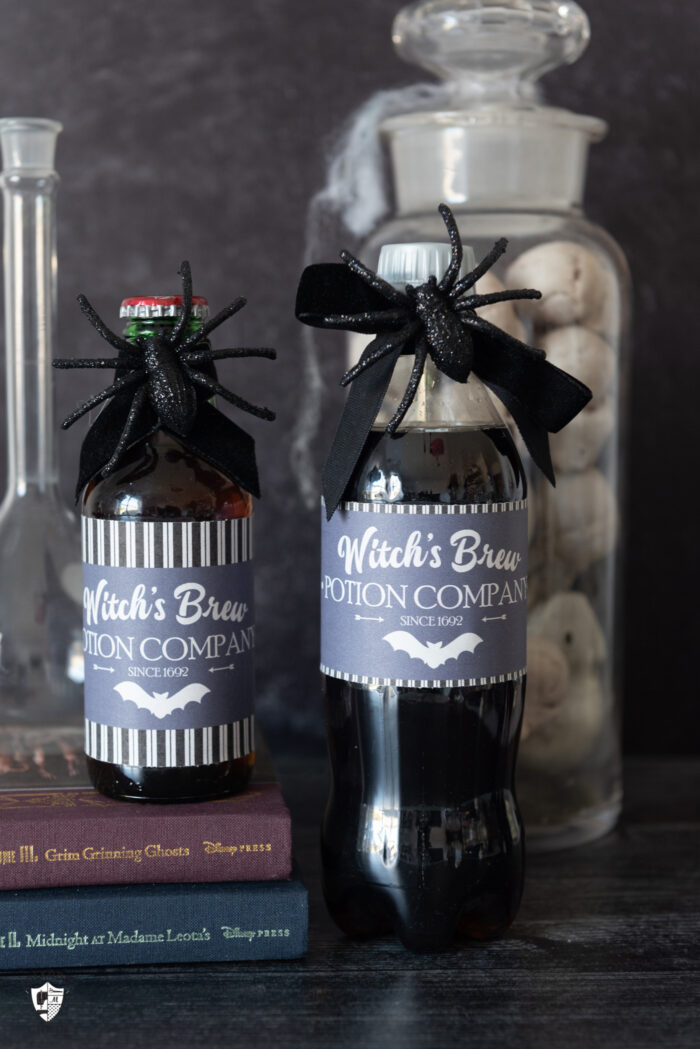 two bottles of diet coke with witches brew labels dark table