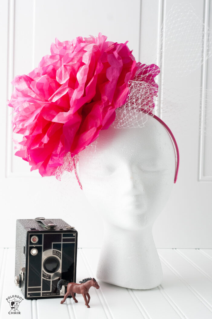 pink paper flower fascinator on white head on white background
