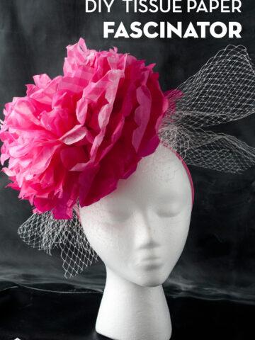 pink paper flower fascinator on white head on black background