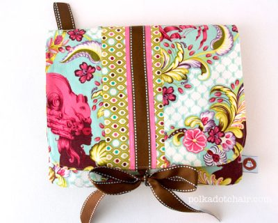 Pink, blue and brown padded ipad case on white table.