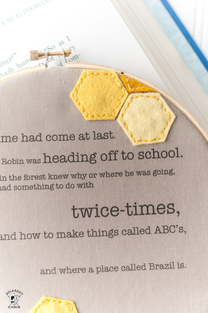 winnie the pooh quote framed in embroidery hoop on book and white table