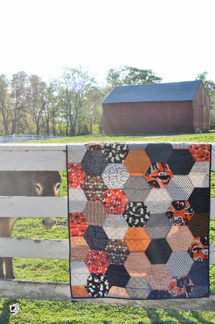 close up of large hexagon quilt with orange, ivory and gray blocks