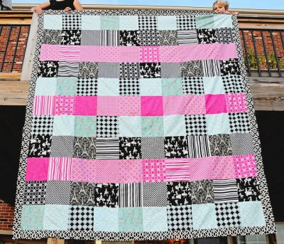 pink, aqua and black queen sized quilt hanging on deck