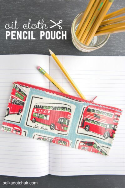 Oil cloth pencil pouch in red and turquoise on white notebook.