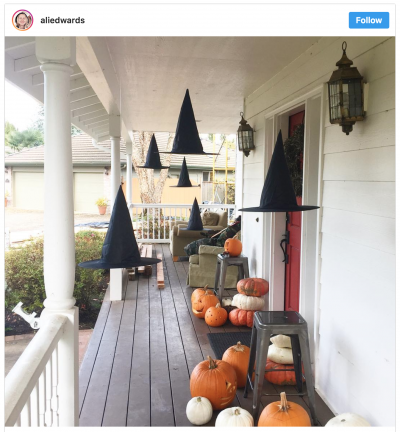Instagram screen shot of witch hat luminaires on a front porch with pumpkins.