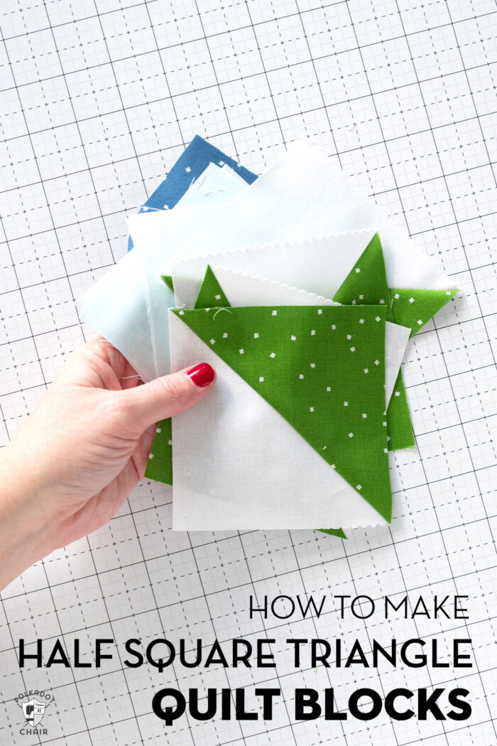 hand holding white, green and blue quilt blocks on white cutting mag