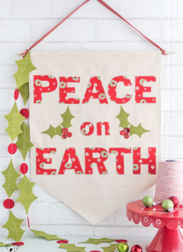 "Christmas DIY Canvas banner with free pattern and templates. How to make a canvas banner- a cute Christmas sign that says ""Peace on Earth"" #Christmas #canvasbanner #DIY #ChristmasCrafts"