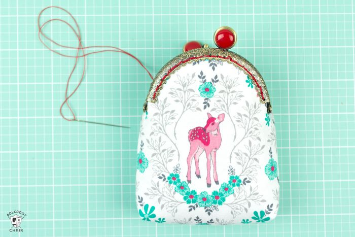 hand stitching purse to frame