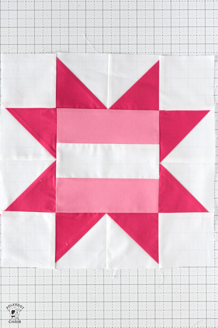 Light pink and dark pink Quilt block on white table.