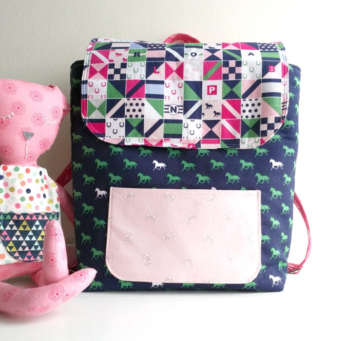 Learn how to sew a mini backpack with this cute toddler backpack pattern. Stitched up with Derby Day fabrics from Riley Blake Designs #minibackpack #toddlerbackpack #smallbackpack #backpacksewingpattern