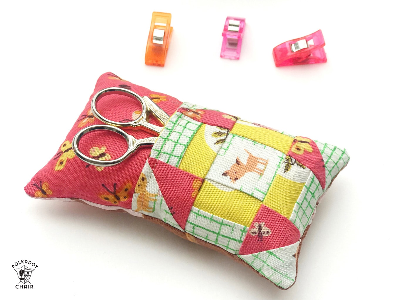 Learn how to make a cute pincushion with a pocket to hold your scissors! A free pincushion sewing tutorial- love the churn dash quilt block addition! #pincushions #DIYpincusions #pincushionstosew #pincushionpatterns #Cutepincushions #sewingtutorial #sewing