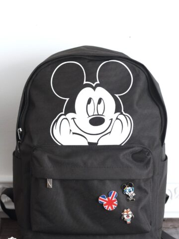 black backpack with mickey mouse iron on sitting on table in front of white wall