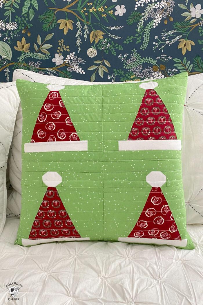 green santa hat pillow on white bed