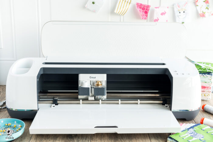 Cricut machine on wood table with fabric
