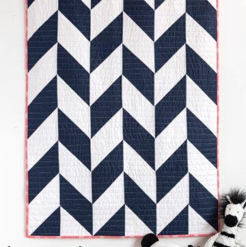 navy and white herringbone quilt on white wall