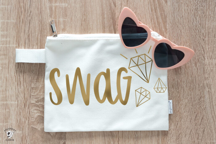 Swag Cricut SVG file cut out with gold iron on vinyl on white bag on tabletop with pink heart sunglasses