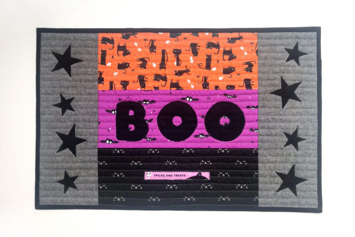 quilted halloween placemat on table with halloween decorations