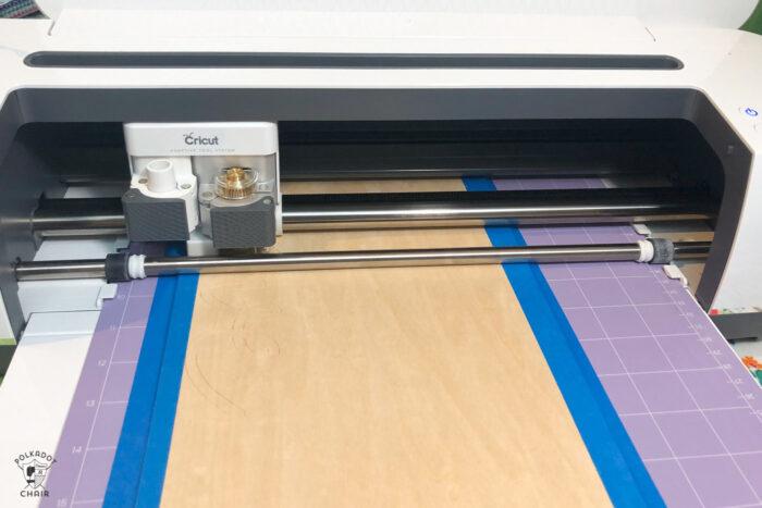 Cricut machine cutting basla wood on purple cutting mat