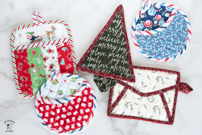 Variety of quilted potholders on white table.