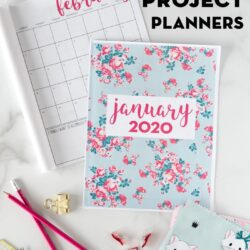 Printable project planner on white table with fabric, pencils and calendar