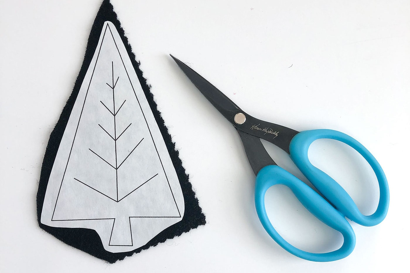 black tree cut from wool with scissors on white table