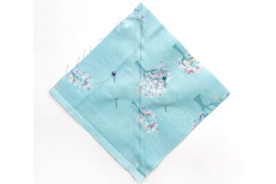 blue square of fabric with line drawn diagonally on white table