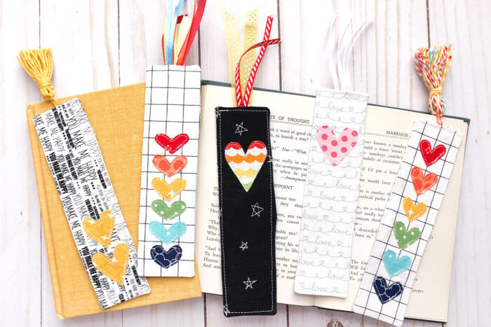 Colorful fabric bookmarks on books on white wood table.
