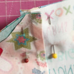 two quilt blocks pinned together along seam