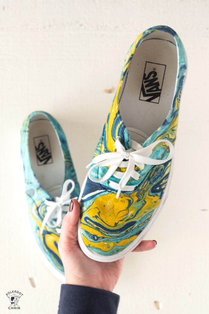 blue and yellow hydro dipped vans being held in hand