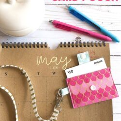 pink keychain card pouch on brown calendar on white tabletop