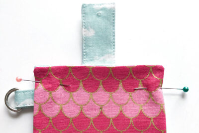 pink rectangle with small blue rectangle snap holder on top on white table