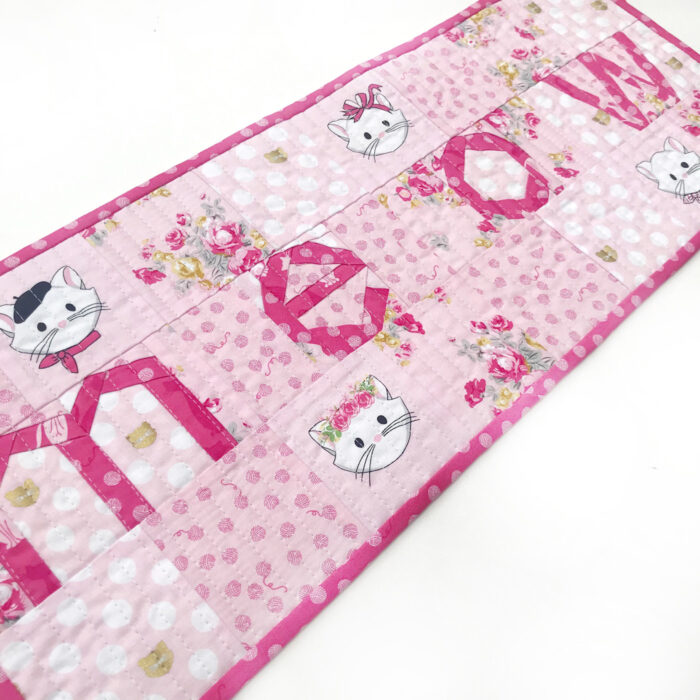 Pink and white MEOW quilted table runner on white tabletop
