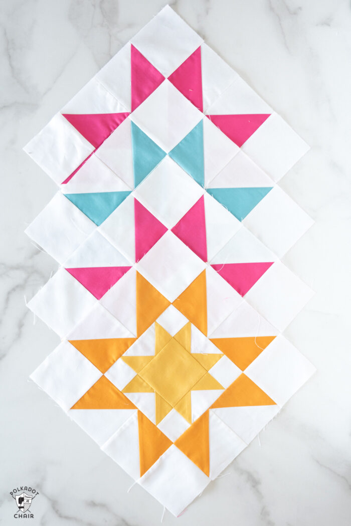 sawtooth star quilt blocks in blues, pinks and yellows on white tabletop