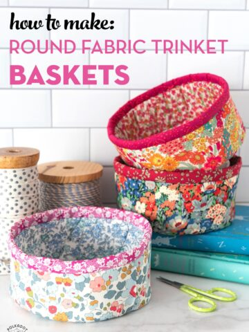 Round fabric baskets on stacked on books with white background