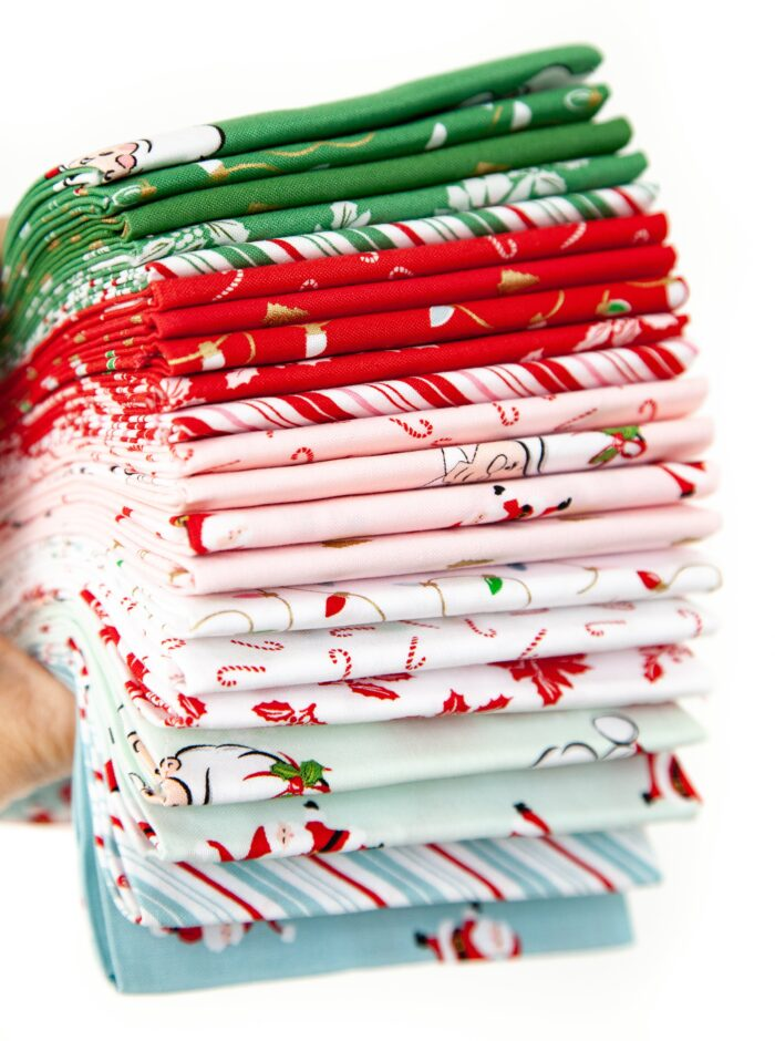 photo of a stack of folded santa claus lane fabric on white background
