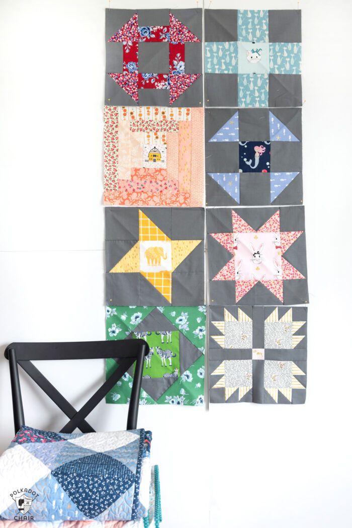 quilt blocks in various colors pinned to white wall