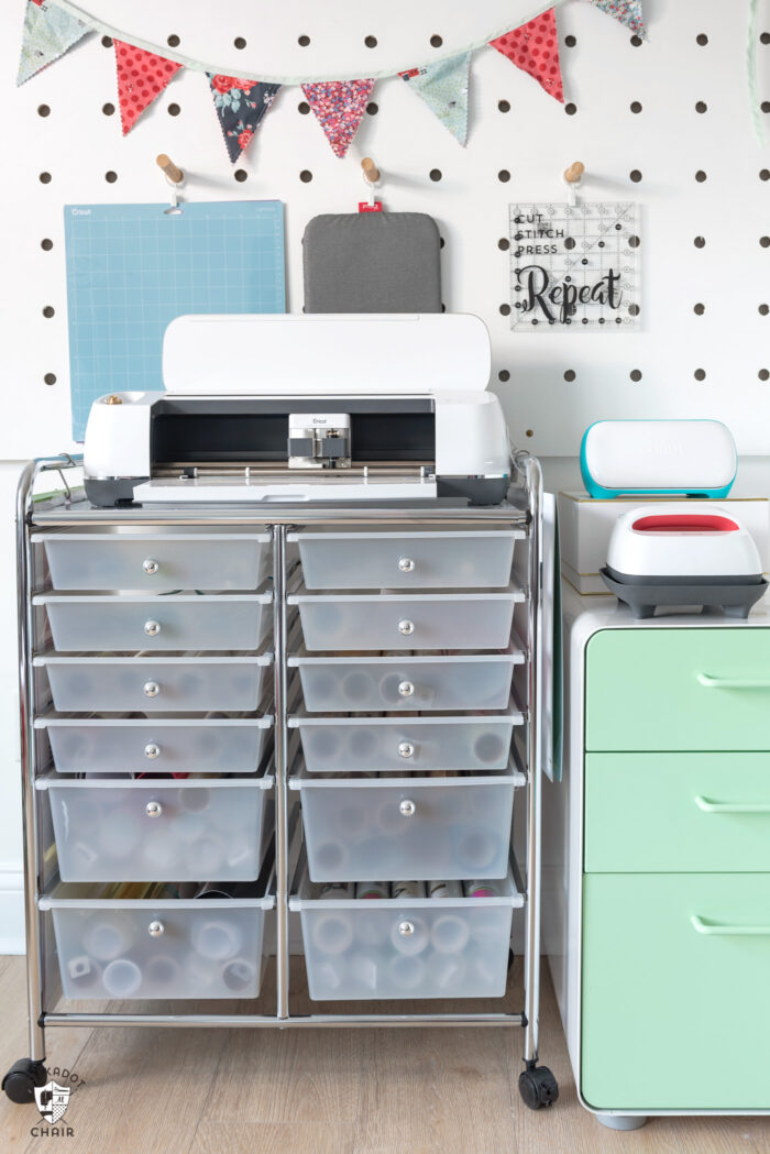 Cricut maker on metal cart in front of peg wall