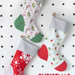 Red, blue and aqua christmas stockings on white peg board