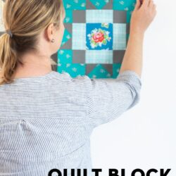 woman placing quilt block on white wall