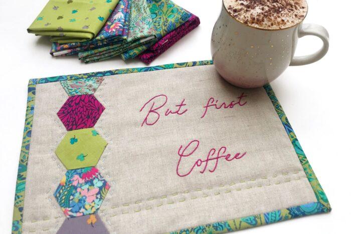 tan and jewel tone mug rug on white table with coffee and fabric