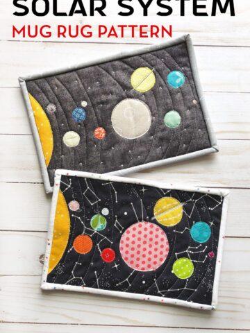 Colorful fabric Solar System mug rug on white wood table