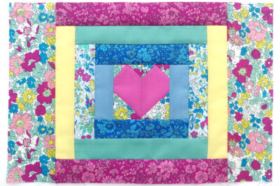 completed heart quilt block on white table