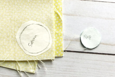 circle applique pieces ironed onto yellow fabric on white table