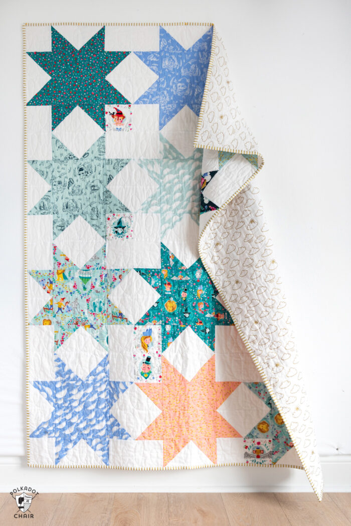 Quilt with folded over top corner hanging on white wall
