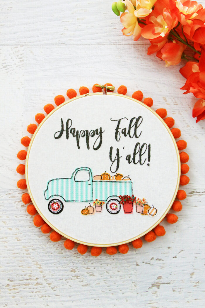 fall embroidery hoop art with truck & pumpkin motifs with pom pom edging.