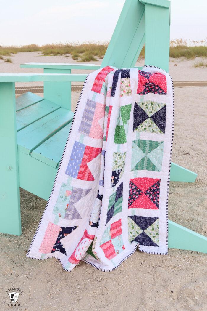 seas the day nautical quilt on giant blue beach chair on beach