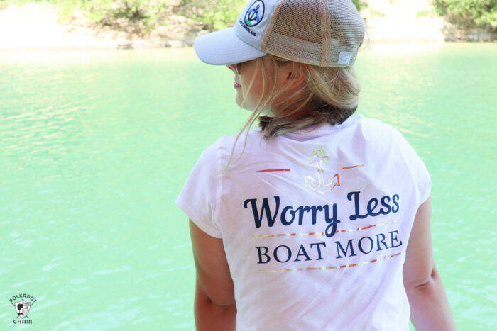 girl on boat looking out to lake wearing white t-shirt