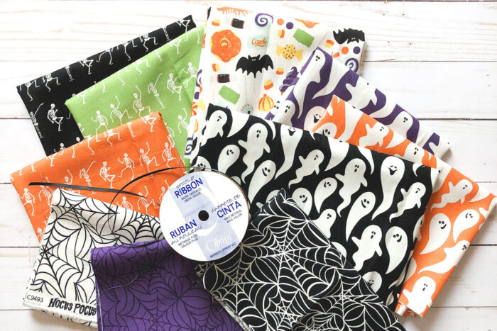 various multi colored halloween fabrics on white table