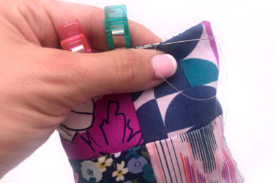 hands pinching seam closed with needle
